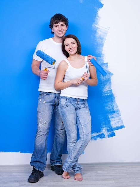 Портрет счастливой молодой влюбленной пары с кистями возле окрашенной стены Бесплатные Фотографии