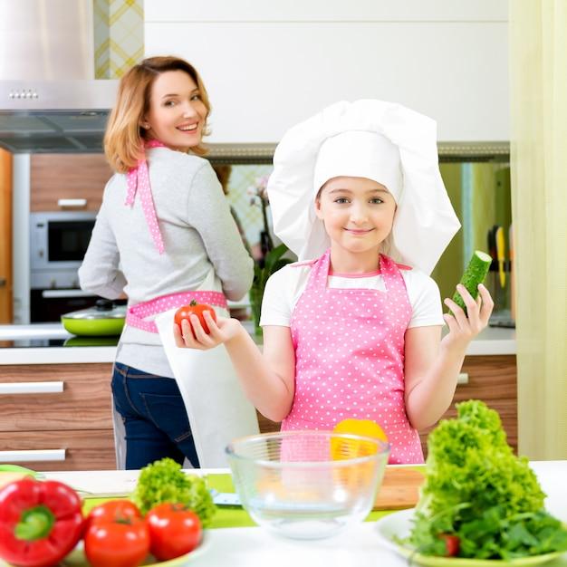 キッチンで調理するピンクのエプロンで娘と幸せな若い母親の肖像画。 無料写真