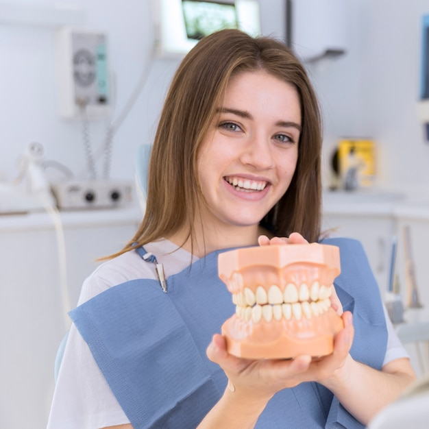 Portrait of happy young woman holding denture in her hands Free Photo