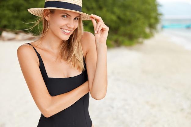 幸せな若い女性の肖像画は水着と夏の麦わら帽子を着て、ビーチの上を歩く 無料写真