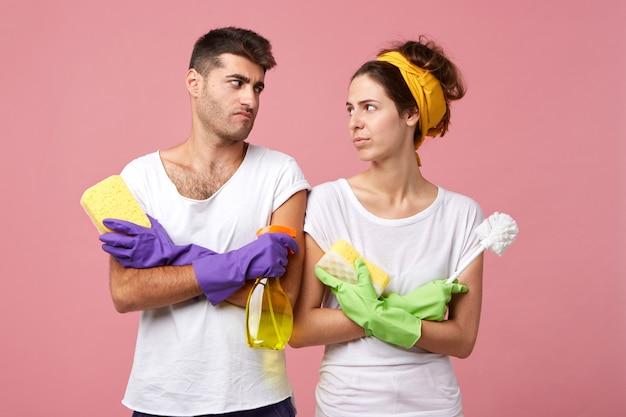 スポンジ、スプレー、ブラシを押しながら何を掃除するかわからないまま、不満そうな顔でお互いを見ている勤勉なカップルの肖像画。毎日のルーチンを持っている不満のカップル 無料写真