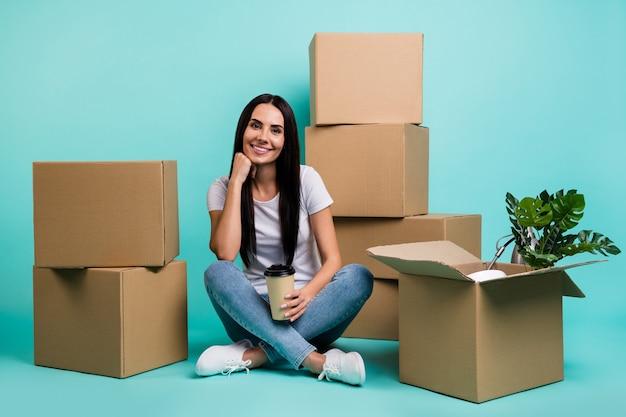 Портрет ее красивой привлекательной веселой брюнетки, сидящей на полу с кучей коробок и пьющих какао Premium Фотографии