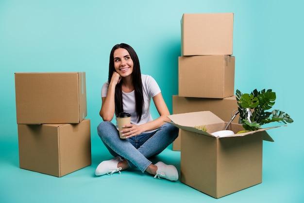 Портрет ее красивой привлекательной веселой мечтательной брюнетки, переезжающей за границу, сидя на полу с кучей коробок Premium Фотографии