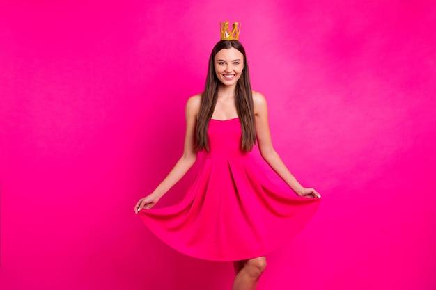 Портрет ее милая привлекательная милая великолепная веселая веселая длинноволосая девушка в платье с короной позирует изолирована на ярком ярком фоне яркого розового цвета фуксии Premium Фотографии