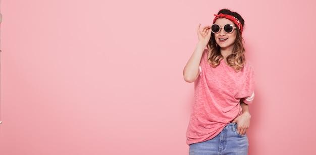 Портрет хипстерской девочки в очках на розовой стене Premium Фотографии