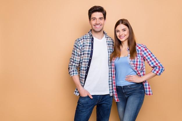 Портрет его он ее она милая привлекательная очаровательная прекрасная романтическая веселая веселая пара в клетчатой рубашке, обнимая проводить отпуск, изолированные на бежевом фоне пастельных тонов Premium Фотографии