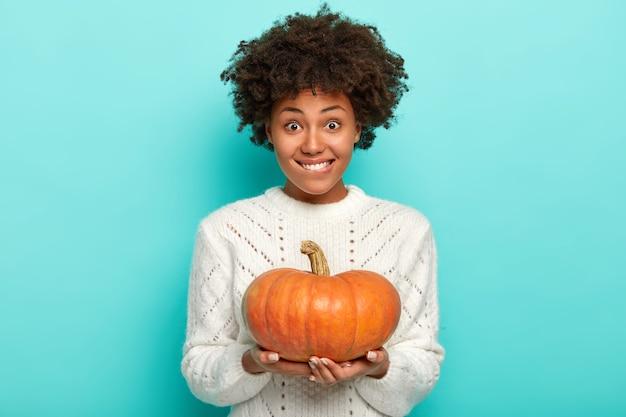 Портрет домохозяйки с вьющимися волосами, одет в теплый удобный свитер, приятно улыбается, держит тыкву обеими руками, готовится к дню благодарения Бесплатные Фотографии