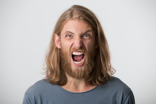 Портрет истерично раздраженного бородатого молодого человека со светлыми длинными волосами в серой футболке выглядит сумасшедшим и кричит изолированно над белой стеной Бесплатные Фотографии