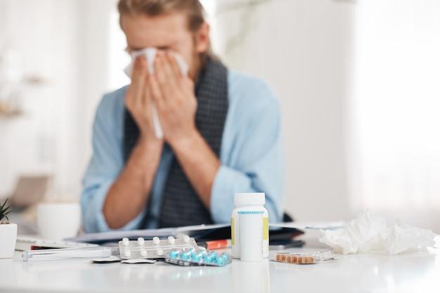 病気の肖像画、病気のひげを生やした男性のくしゃみや咳、ハンカチを使用して、鼻をこすります。男は鼻水、咳、ひどい風邪をひいており、錠剤、薬物、ビタミンに囲まれた職場に座っています。 無料写真