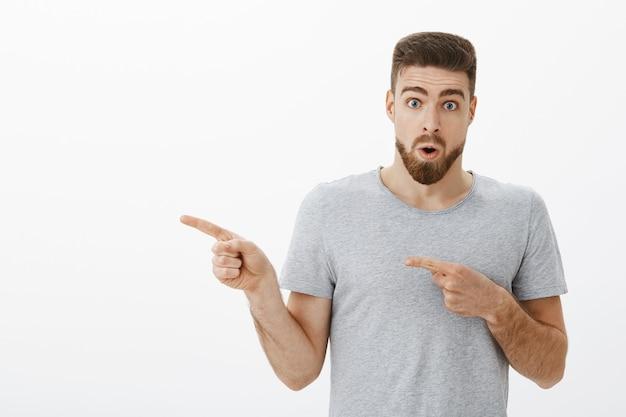 Портрет впечатленного и удивленного заинтересованного красивого зрелого мужчины с бородой, задыхающегося, складывающихся губ в вау-звуке, указывающего влево, спрашивают о любопытном новом парикмахерском, открывшемся рядом с белой стеной Бесплатные Фотографии