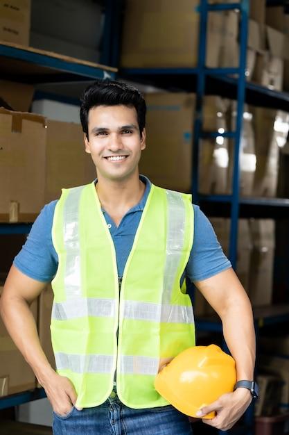 安全ベストスタンドと黄色いヘルメットを保持しているインドのアジアの倉庫作業員の肖像画 Premium写真