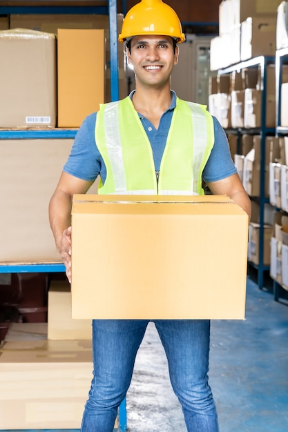 インドの倉庫作業員の肖像画は段ボール箱の包装を保持します Premium写真