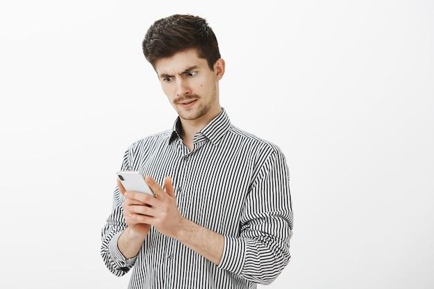 口ひげと激しい混乱している普通のヨーロッパの男性モデルの肖像画、スマートフォンの画面で質問されている、奇妙なメッセージを受け取っている、または銀行口座からのお金がどこに行ったのか無知である 無料写真