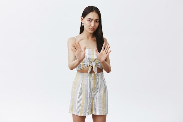 Портрет очень недовольной и встревоженной симпатичной азиатской девушки в соответствующей одежде, держащей ладони возле груди в жесте «нет» или «стоп», отказывающейся попробовать алкоголь Бесплатные Фотографии