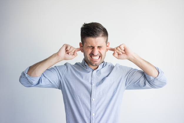 Portrait of irritated young man plugging ears with fingers. Free Photo