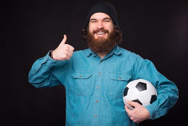 Портрет радостного бородатого хипстера, показывающего большой палец вверх и держащего футбольный мяч Premium Фотографии