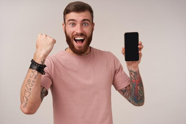 広い陽気な笑顔で携帯電話を手に保ち、イエスのジェスチャーで拳を上げ、白で隔離の楽しい入れ墨の剃っていないブルネットの男の肖像画 無料写真