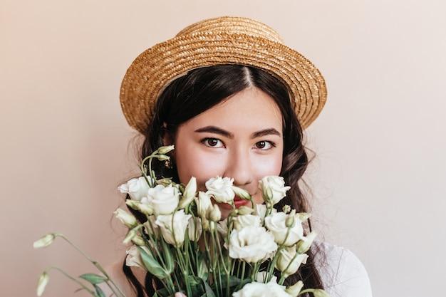 花を持ってカメラを見ている韓国の女性の肖像画。白いトルコギキョウと麦わら帽子のアジアの女性のスタジオショット。 無料写真