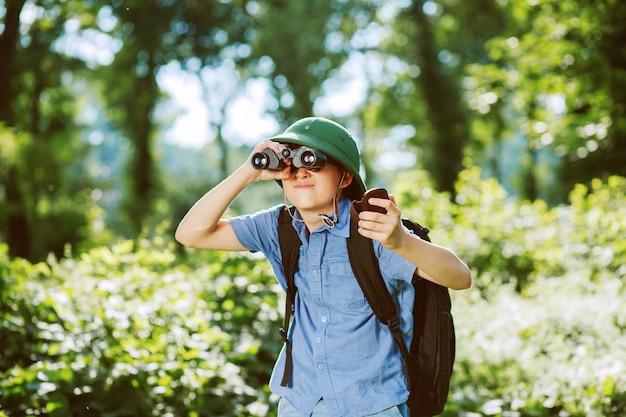 Портрет маленького исследователя с биноклем в лесу. Premium Фотографии