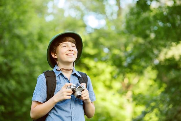 Портрет маленького исследователя с фотоаппаратом в лесу. Premium Фотографии