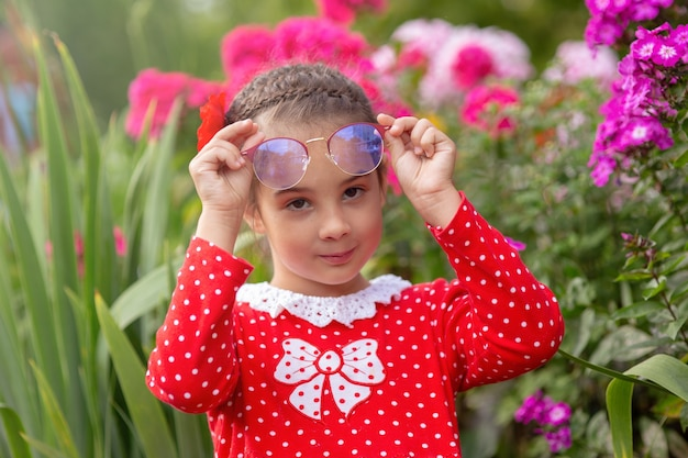メガネの水玉模様の赤いドレスの少女の肖像画 Premium写真