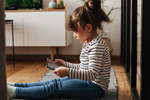 Портрет маленькой женщины в джинсах и футболке, сидящей на ковре и держащей таблетку. Бесплатные Фотографии
