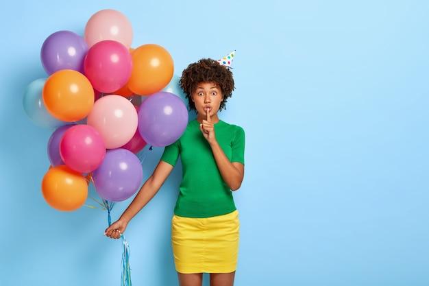 Портрет прекрасной афроамериканки делает жест молчания, держит букет разноцветных шаров, носит зеленую футболку и желтую юбку, рассказывает секрет Бесплатные Фотографии