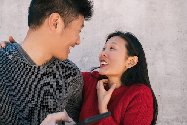 Портрет милой азиатской пары, смотрящей на мобильный телефон, проводя хорошее время вместе. концепция любви и технологии. Premium Фотографии