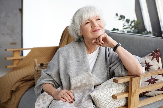 Портрет прекрасной седой европейской женщины средних лет с мечтательной улыбкой и глазами, полными мудрости, расслабляющейся в одиночестве дома, сидя на удобном диване, вспоминая дни своей молодости Бесплатные Фотографии