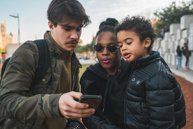 楽しんで、リラックスして、屋外の公園で携帯電話を使用して素敵な混血民族家族の肖像画。 無料写真