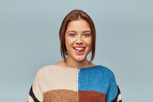 舌を出して上唇をなめる現代の髪型を持つ素敵な女性の肖像画 無料写真