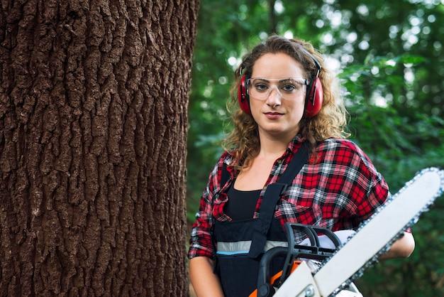 Портрет лесоруба-лесоруба, стоящего у ствола дерева в лесу с бензопилой Бесплатные Фотографии