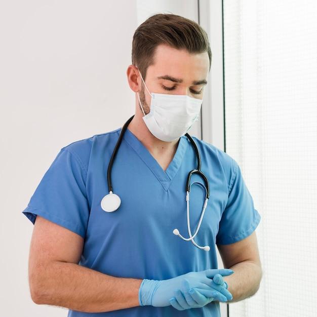 手袋とマスクを身に着けている男性看護師の肖像画 無料写真
