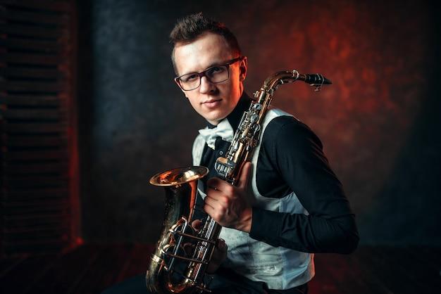 Портрет мужчины-саксофониста с саксофоном, джазмена с саксофоном. Premium Фотографии