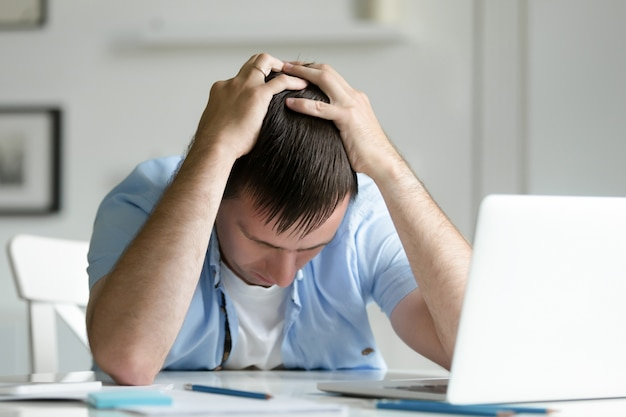 Portrait of man grabbing his head in despair near laptop Free Photo