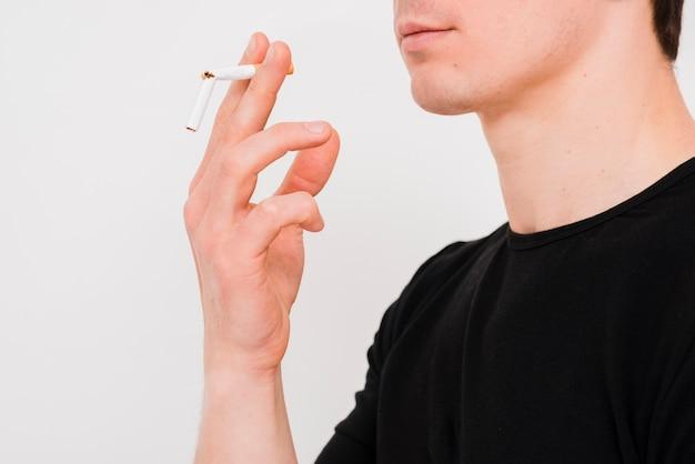 Портрет мужчины с разбитой сигаретой на белой стене Бесплатные Фотографии
