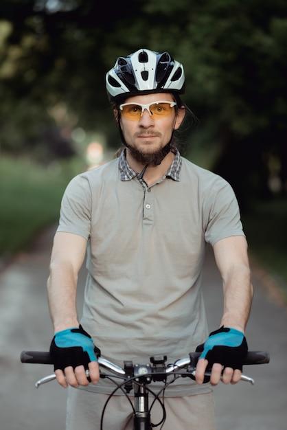 노란색 선글라스와 헬멧 도로에 자전거와 함께 서서 정면으로 보는 남자의 초상화 프리미엄 사진