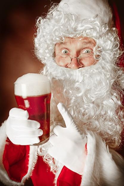 맥주와 함께 빨간색에서 고급스러운 흰 수염, 산타의 모자 및 빨간색 의상과 함께 산타 클로스 의상을 입은 남자의 초상화 무료 사진