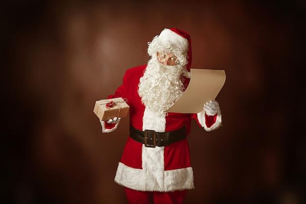 Портрет мужчины в костюме санта-клауса - с роскошной белой бородой, шляпой санта-клауса и красным костюмом читает письмо на красном фоне студии с подарками Бесплатные Фотографии