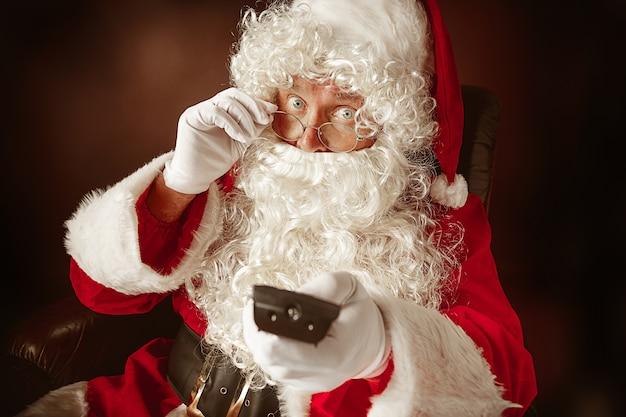 Портрет мужчины в санта-клаусе с роскошной белой бородой, шляпой санта-клауса и красным костюмом на красном фоне студии Бесплатные Фотографии