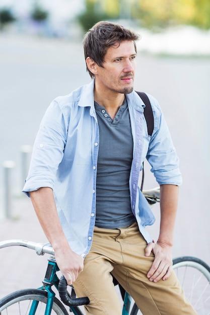 Портрет мужчины, позирующего со своим велосипедом Бесплатные Фотографии
