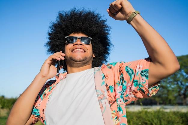 電話で話し、路上で屋外で良いニュースを祝う男の肖像画 Premium写真