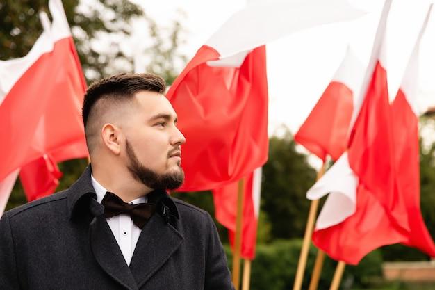 Портрет мужчины с флагами польши позади Premium Фотографии