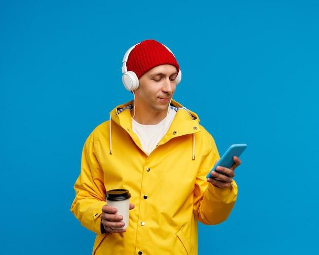 Портрет мужчины с телефоном, слушающим музыку и пьющим кофе Premium Фотографии