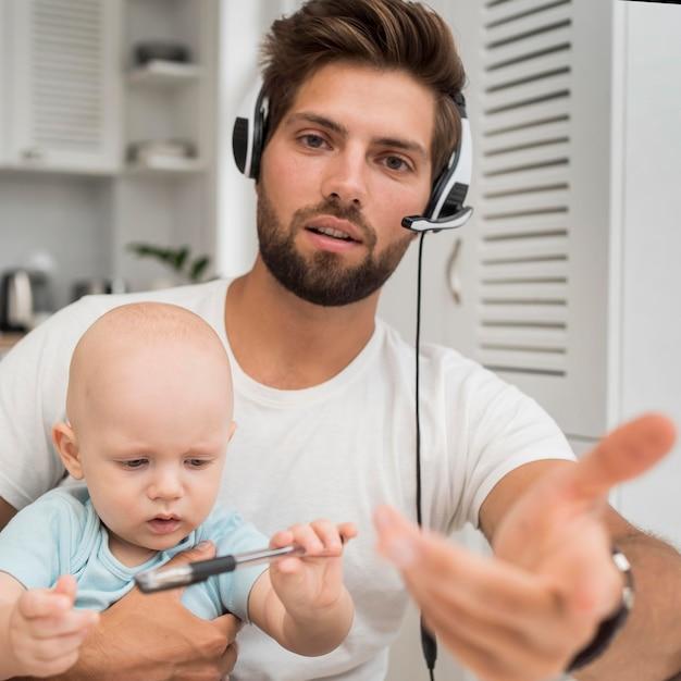 Портрет мужчины, работающего с ребенком на руках Бесплатные Фотографии