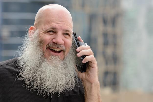 야외 도시의 전망에 대해 긴 수염을 가진 성숙한 대머리 힙 스터 남자의 초상화 프리미엄 사진