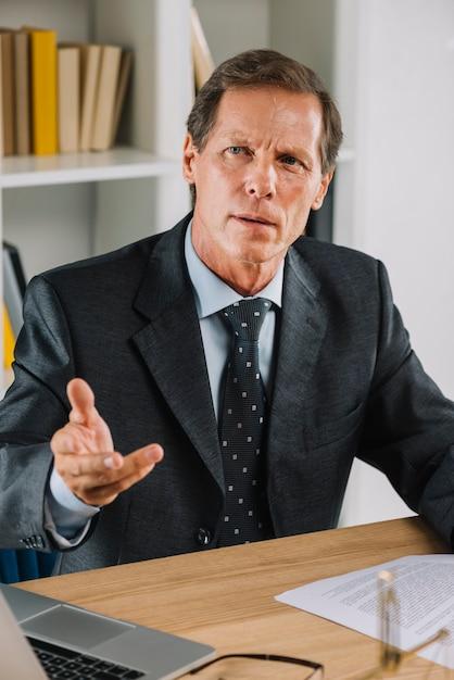 Портрет зрелого бизнесмена на рабочем месте gesturing Бесплатные Фотографии