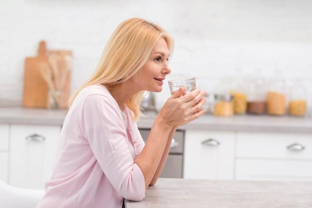 水のガラスを飲む成熟した女性の肖像画 Premium写真