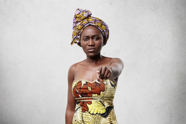 頭にスカーフを身に着けているほっそりした姿と真剣な表情の人差し指であなたを指している白いコンクリートの壁に立っている美しいドレスを持つ中年の黒人女性の肖像画 無料写真