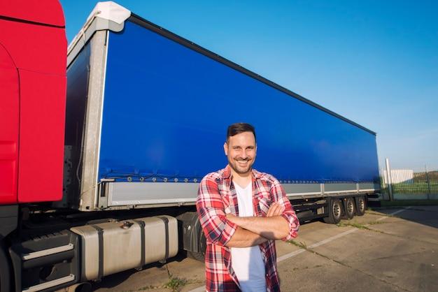 運転の準備ができてトラックトレーラーのそばに立って腕を組んで中年のトラック運転手の肖像画 無料写真